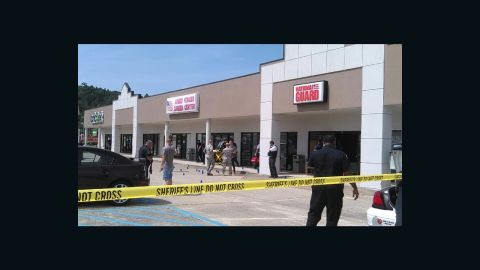 """Blue evidence markers, believed to be the location of spent shell casings, can be seen here. Gina Mule, a server at a restaurant who took this photo, said she saw a man in a car firing a """"high-powered rifle"""" at the recruiting offices at about 10:50 a.m. ET Thursday."""