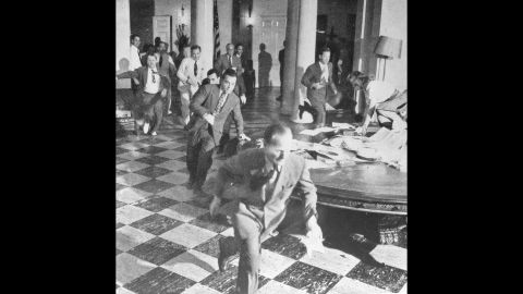 Members of the White House Press Corps rush to telephones after Truman announced Japan's surrender on August 15, 1945.