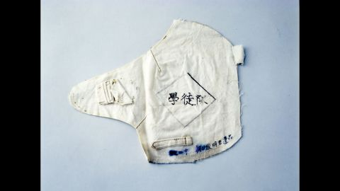 """Toshiaki Asahi was a 13-year-old high school student who was working at the time of the attack and wearing this armband. Despite serious burns, he managed to make his way through fires sparked by the bomb. He climbed up a riverbank and escaped to the outskirts of the city. There he was found by an acquaintance and carried home. Three days later, he told family members, """"Thank you for all you've done,"""" and died in his mother's lap."""