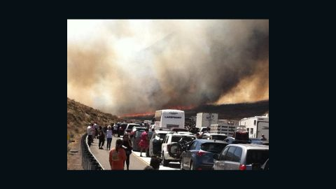 Bystanders look on along Interstate 15 on the Cajon Pass, Friday, July 17, 2015, near San Bernadino, Calif., as a fast-moving wildfire swept across the Southern California freeway, destroying numerous vehicles and sending motorists running to safety before burning at least five homes. (Arsenio Alcantar via AP)
