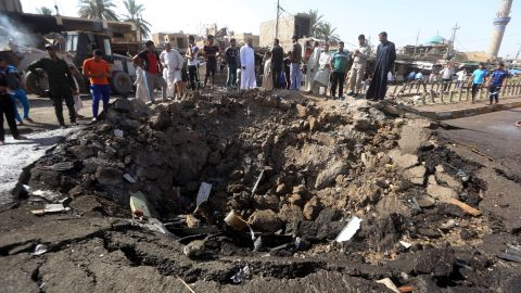 Iraqi men look at a crater left by a massive suicide car bomb attack carried out Friday in Khan Bani Saad.