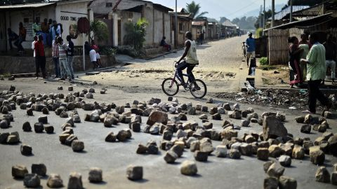 """A man rides past a barricade set up by protesters in Bujumbura on July 21. Animosity against Nkurunziza <a href=""""http://www.cnn.com/2015/05/14/world/gallery/burundi-unrest/index.html"""" target=""""_blank"""">boiled over in April</a> when he expressed his intention to run for a third term. There have been protests and a failed coup."""