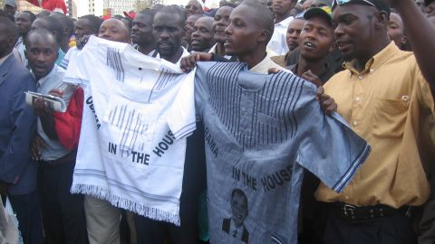 The Obama brand was popular across Africa, too, with these admirers holding up shirts as they watched Obama pass.