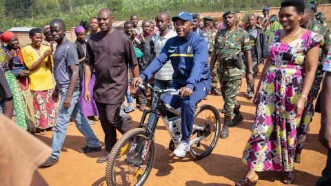 Nkurunziza is accompanied by first lady Denise Bucumi Nkurunziza, right, as he arrives on a bicycle to cast his vote in Ngozi, Burundi, on Tuesday, July 21.