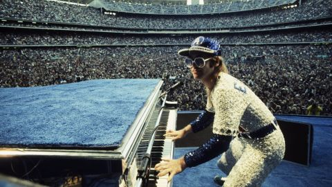 """John's pop triumph came from a series of hits in the early '70s, including """"Tiny Dancer,"""" """"Your Song"""" and """"Bennie and the Jets,"""" the bar-room singalong that, somehow, no one knows the words to. He's best known for his stadium tours, playing to sold out crowds in extravagant, glittering costumes and his signature tinted sunglasses."""