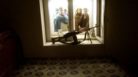 Afghans look into Omar's bedroom as they go through his compound on the outskirts of Kandahar on December 11, 2001.