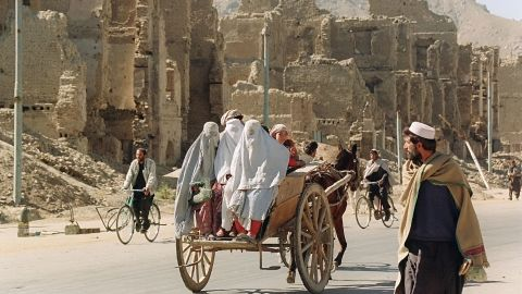 Three women hitch a ride on the back of a donkey cart as they pass by the ruins of Kabul's former commercial district in November 1996.