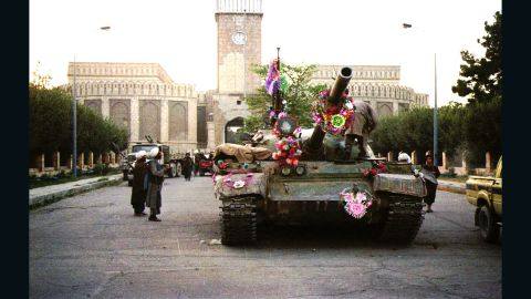 Tanks manned by Taliban fighters are decorated with flowers in front of the presidential palace in Kabul on September 27, 1996.