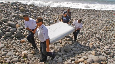 """On July 29, police carry a piece of <a href=""""http://www.cnn.com/2015/07/30/world/gallery/debris-found-reunion-island/index.html"""" target=""""_blank"""">debris on Reunion Island,</a> a French territory in the Indian Ocean. A week later, authorities confirmed that the debris was from the missing flight."""