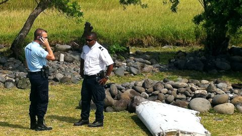 A policeman and a gendarme stand next to a piece of debris from an unidentified aircraft found in the coastal area of Saint-Andre de la Reunion, in the east of the French Indian Ocean island of La Reunion, on July 29, 2015.