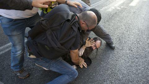 Police wrestle Schlissel to the ground and arrest him.