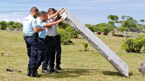 """In this photo dated Wednesday, July 29, 2015, French police officers inspect a piece of debris from a plane in Saint-Andre, Reunion Island. Air safety investigators, one of them a Boeing investigator, have identified the component as a """"flaperon"""" from the trailing edge of a Boeing 777 wing, a U.S. official said. Flight 370, which disappeared March 8, 2014, with 239 people on board, is the only 777 known to be missing. (AP Photo/Lucas Marie)"""
