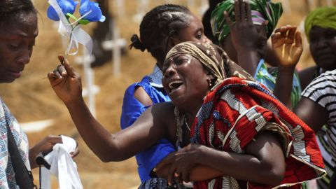 Relatives weep for a loved one who it was believed died from Ebola, at a graveyard on the outskirts of Monrovia on March 11, 2015.