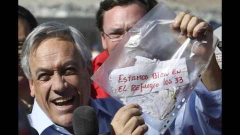 """Chilean President Sebastian Pinera holds up a plastic bag containing a message from the miners on August 22. Translated from Spanish, it read: """"We are OK in the refuge, the 33."""" The miners were confirmed to be alive when rescue teams reached them via a tube that was sent down a small hole. The same hole was used to provide the miners with food, supplies and letters."""