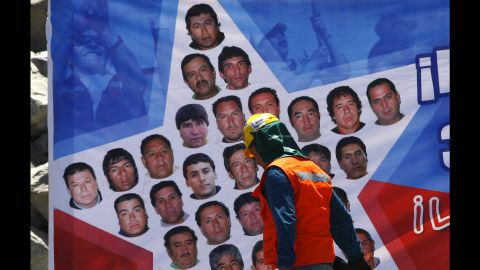 A rescue worker walks past a banner with pictures of the trapped miners on October 11.