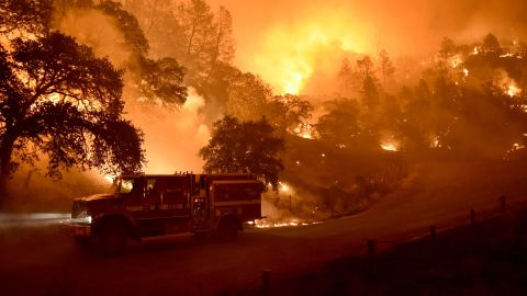 A Cal Fire truck is driven away from flames as the Rocky Fire burns near Clearlake on August 2.
