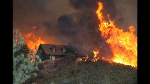 Flames approach a house in Lower Lake on Friday, July 31.