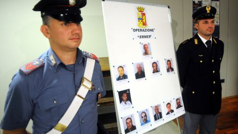 Italian authorities stand next to mugshots of 11 men suspected of helping Matteo Messina Denaro.
