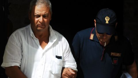 An Italian police officer walks with one of the suspects in Palermo.