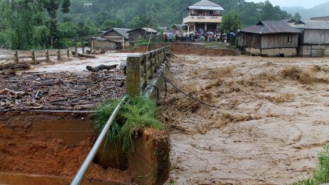People look at a bridge which was washed away by floodwater in the state of Manipur, India on August 1, 2015. At least 178 have been killed in recent flooding, with an estimated 10 million affected across India.