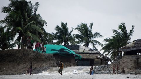 Bangladeshi villagers wade through flood waters in Cox's Bazar.