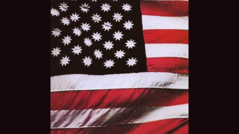 """<strong>""""There's a Riot Goin' On,"""" Sly and the Family Stone</strong>: Steve Paley's photograph of an American flag with suns in place of stars (on a black field) served as the cover of Sly's 1971 album, but in later years it was replaced by <a href=""""http://ecx.images-amazon.com/images/I/51jVueymJML._SY300_.jpg"""" target=""""_blank"""" target=""""_blank"""">a picture of the band in concert</a>."""