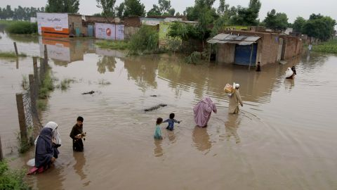 Pakistani villagers wade through floodwaters caused by heavy rains at a village on the outskirts of Nowshera near Peshawar, Pakistan, Sunday, Aug. 2, 2015. Flooding has left millions displaced throughout the region.