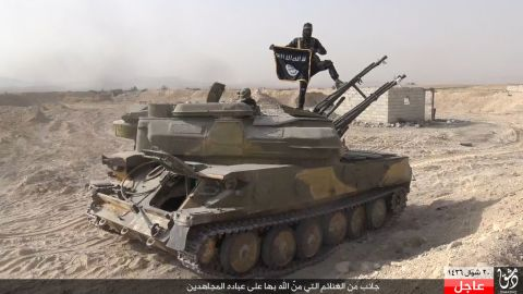 """In this image taken from social media, an ISIS fighter holds the group's flag after the militant group <a href=""""http://www.cnn.com/2015/08/07/world/syria-isis-al-qaryatayn-christians/index.html"""" target=""""_blank"""">overran the Syrian town of al-Qaryatayn</a> on Thursday, August 6, the London-based Syrian Observatory for Human Rights reported. ISIS uses modern tools such as social media to promote reactionary politics and religious fundamentalism. Fighters are destroying holy sites and valuable antiquities even as their leaders propagate a return to the early days of Islam."""
