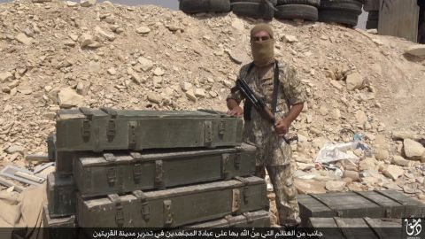 An ISIS fighter poses with spoils purportedly taken after capturing the Syrian town of al-Qaryatayn.
