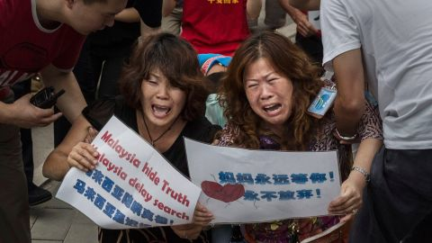 BEIJING, CHINA - AUGUST 07: Chinese relatives of passengers missing on Malaysian Airlines flight MH370 cry as they kneel in front of the media outside the Malaysian Embassy during a protest by relatives on August 7, 2015 in Beijing, China. France expanded its search for debris off Reunion Island Friday a day after Malaysia's prime minister announced that a piece of wing discovered last week is from Malaysia Airlines Flight MH 370 which vanished last year. Officials and experts from other countries including the United States and Australia have been more cautious, saying that more investigating needs to be done. (Photo by Kevin Frayer/Getty Images)