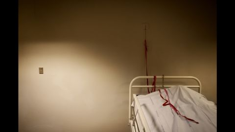 """In the """"Sixhour Room"""" lies a man under a blanket. Ertmann said that before six hours have passed from the moment of his death, a doctor will examine the body, looking for signs of clinical death such as bruising and stiffness. The red cord seen in this photo has never been used in the chapel in Aarhus, but it's<br />there anyway, so that the person under the cloth can call for help should they awaken."""
