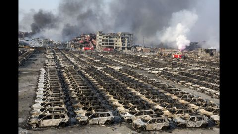 """Smoke from the explosion billows over destroyed cars. As of 2014, Tianjin was the world's 10th-busiest container port, <a href=""""http://www.worldshipping.org/about-the-industry/global-trade/top-50-world-container-ports"""" target=""""_blank"""" target=""""_blank"""">according to the World Shipping Council</a>."""