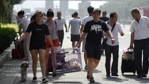 """Residents take their belongings as they evacuate from parts of the city. Managers of the warehouse facility have provided """"insufficient information"""" about what was stored there, a city safety official said, though it is known that sodium cyanide, a highly toxic chemical that can rapidly kill humans exposed to it, was one of the stored materials. <br />"""