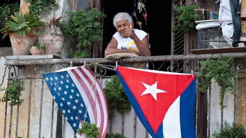 A Cuban gives the thumbs up from his balcony decorated with the US and Cuban flags in Havana, on January 16, 2015. The United States will ease travel and trade restrictions with Cuba on Friday, marking the first concrete steps towards restoring normal ties with the Cold War-era foe since announcing a historic rapprochement. AFP PHOTO/YAMIL Lage        (Photo credit should read YAMIL LAGE/AFP/Getty Images)