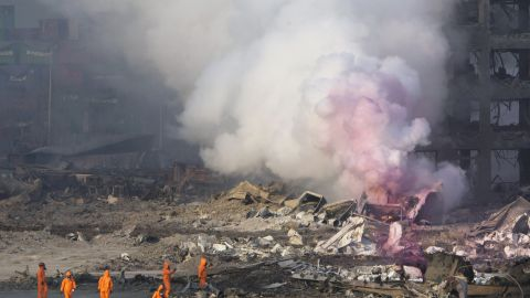 """Firefighters wear protective gear while working as partially pink smoke billows nearby. The environmental group Greenpeace expressed concern """"that certain chemicals will continue to pose a risk to the residents of Tianjin,"""" and city residents shared similar fears on social media."""