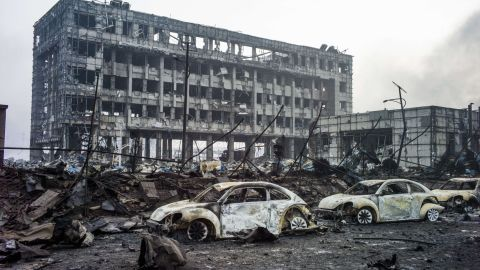 Volkswagens lie burned near ruined buildings on Friday, August 14.