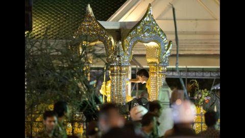 A police officer investigates the scene at the Erawan Shrine.