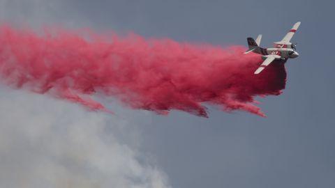 A plane drops fire retardant on the Cabin Fire north of Asuza, California, on Saturday, August 15.