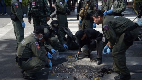 Policemen inspect the cordoned-off site of a bomb blast in the heart of Bangkok's tourist and commercial center on Monday, August 17.
