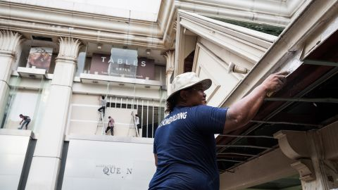 Workers make repairs to the buildings in and around the Erawan Shrine on August 19.