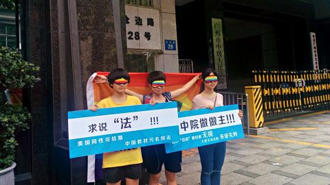 """Chen Qiuyan and her friends outside a court in Guangzhou on July 29, 2015. The board on the left reads: """"Seeking justice. Gay people can get married in the United States, but text books stigmatize them in China."""""""