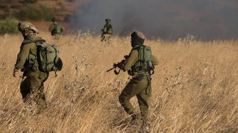 Israeli soldiers inspect a field where rockets fired from Syria landed near Kfar Szold, causing fires but no injuries, in northern Israel, close to the Golan Heights and the border with Lebanon, on August 20, 2015. Israel launched artillery and air strikes against Syrian army positions in the Golan Heights overnight in response to rocket fire that hit the Upper Galilee and the Israeli-annexed side of the Golan Heights, according to Israeli military sources.