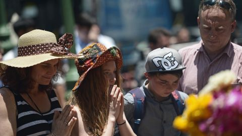 Foreigners offer prayers at the reopened Erawan shrine. Authorities say the perpatrators targeted busy places popular with tourists to damage the economy.