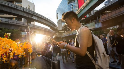 A man offers incense and prays at the Erawan shrine.