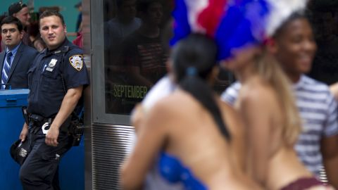 A police officer looks on as women pose for pictures on August 19.