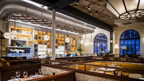 """Built into the walls of London's Old Spitalfields Market, <a href=""""http://www.blixen.co.uk/"""" target=""""_blank"""" target=""""_blank"""">Blixen</a> was a bank in its previous life. Now, it's an informal take on a grand European brasserie featuring a terrazzo-tiled floor mid-century furniture, brass fittings, and seductive walnut bar. The dining room spills out into a plant-filled pergola."""