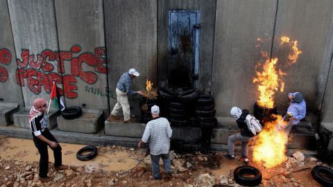 Palestinian youths in 2009 protest near a barrier in a West Bank village.