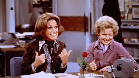 """Mary Tyler Moore (as Mary Richards) (left) gives a """"thumbs up"""" sign as she sits at her desk with Betty White (as Sue Ann Nivens) in a scene from """"The Mary Tyler Moore Show"""" in 1975. Nivens, the """"Happy Homemaker,"""" could make a wicked Veal Prince Orloff and also cut rivals down to size."""