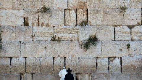 """Pope Francis prays next to a rabbi at the Western Wall in Jerusalem's Old City in May 2014. The Pope went on a <a href=""""http://www.cnn.com/2014/05/24/world/gallery/pope-holy-land/index.html"""">three-day trip to the Holy Land</a>, and he was accompanied by Jewish and Muslim leaders from his home country of Argentina."""