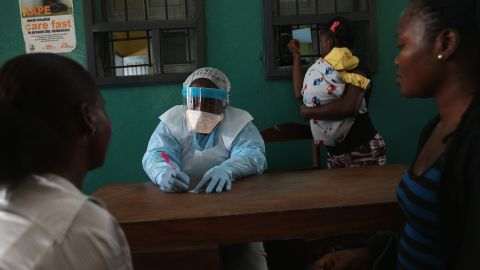 Health workers in protective clothing speak with new arrivals at a hospital in Monrovia, Liberia, on February 2, 2015.